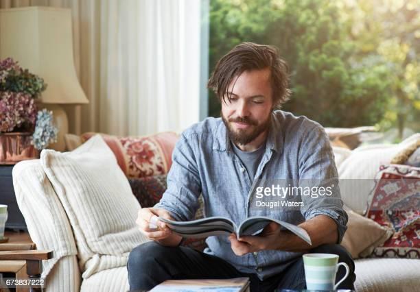 Man reading magazine on sofa at home.