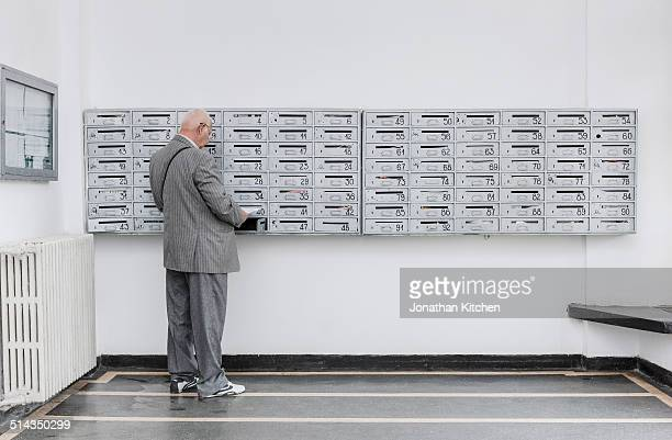 Man reading mail at post box