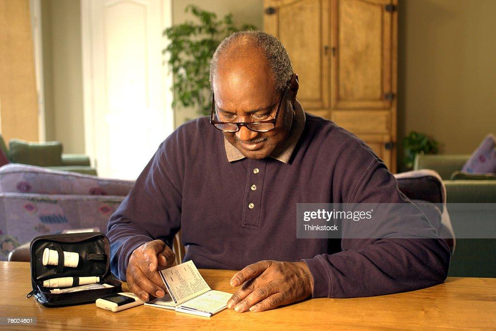 Man reading manual for blood test kit : Stock Photo