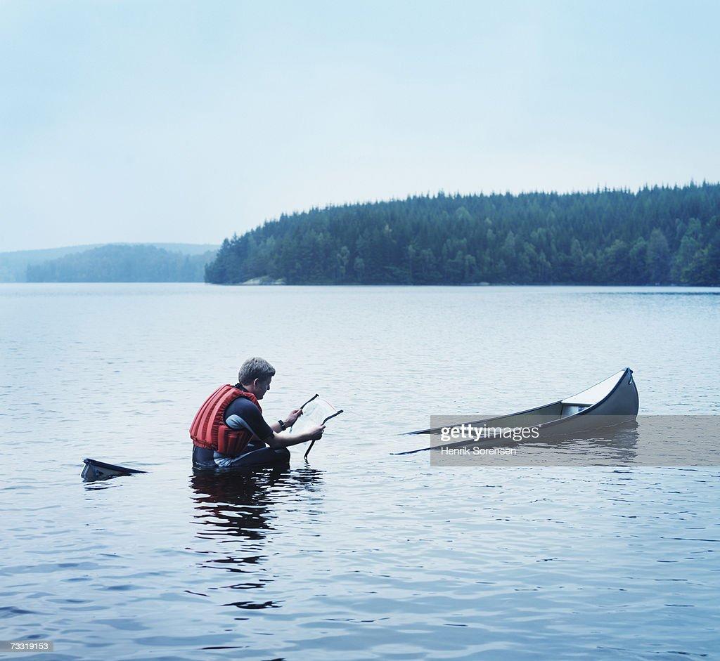 Man Reading Map In Sinking Kayak Side View Stock Photo