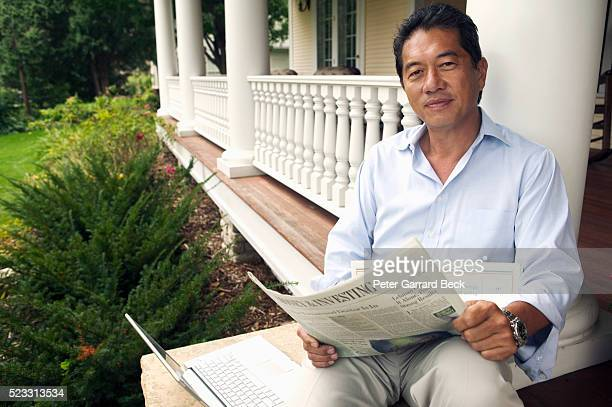 Man Reading Newspaper and Using Laptop on His Porch