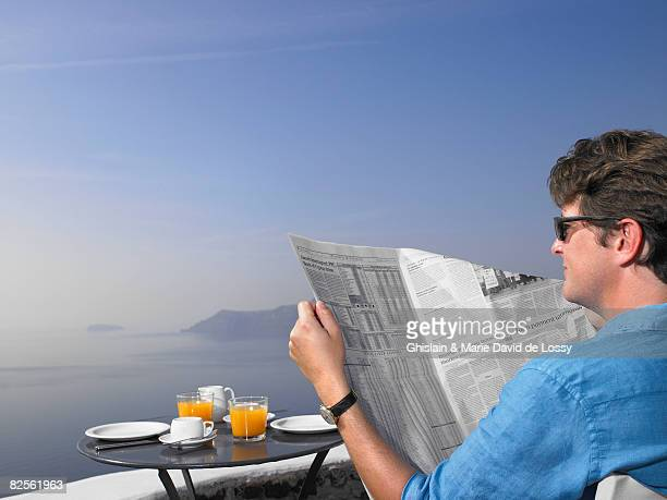 Man reading newspaper at breakfast