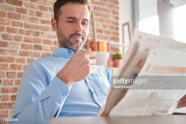 Man reading newspaper drinking coffee