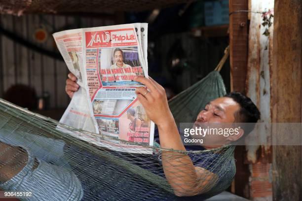 Man reading newspaper in a Hammock Vietnam