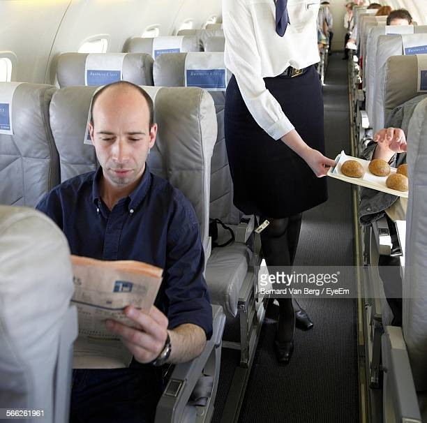 Man Reading Newspaper In Airplane While Stewardess Serving Food