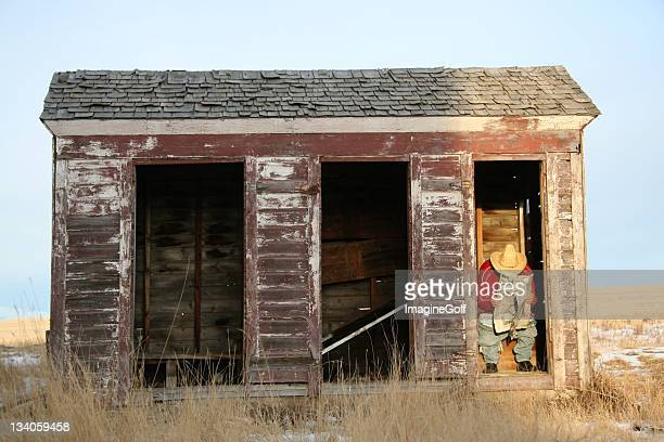 Man Reading Newspaper in an Outhouse