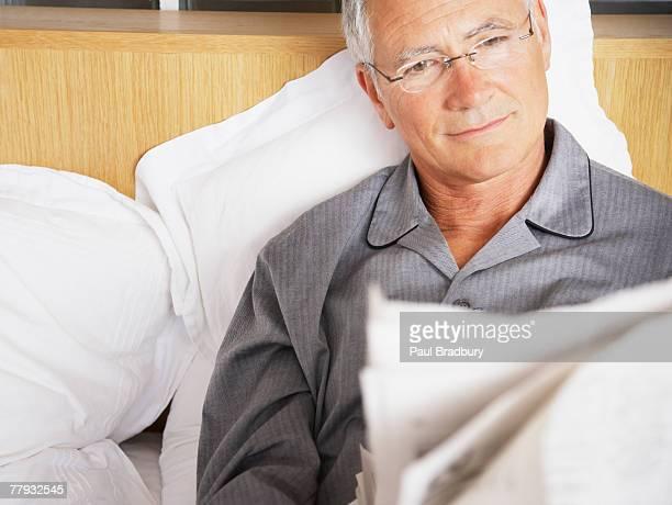 Homme lisant le journal au lit
