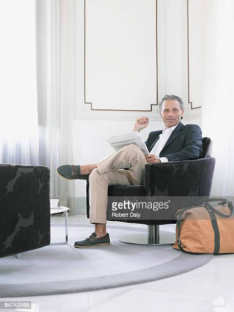 Man reading newspaper in modern hotel suite