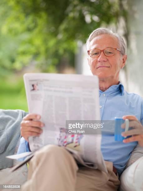 Mann liest Zeitung in Verandaschaukel