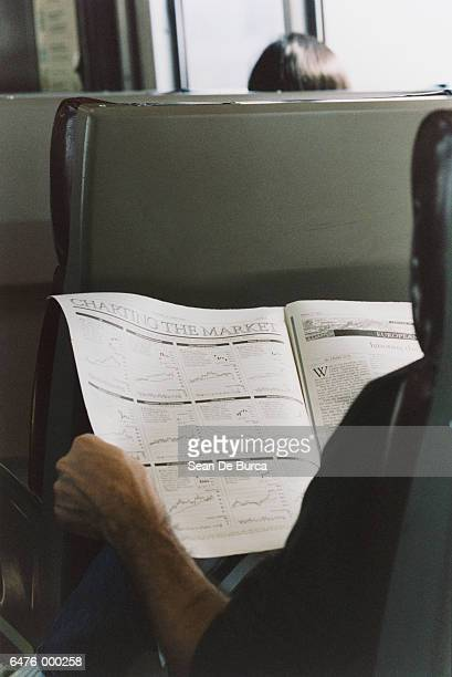 Man Reading Newspaper in Train