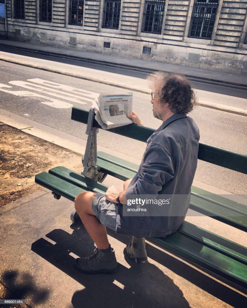 Man reading newspaper on Paris street, France : Stock Photo