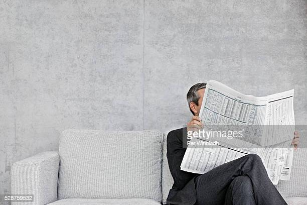 man reading newspaper on sofa - news not politics stock pictures, royalty-free photos & images