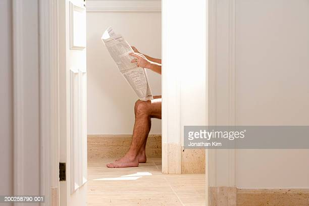 Man reading newspaper on toliet, side view