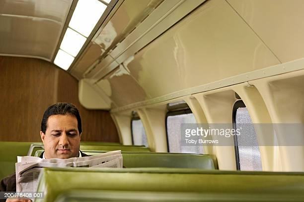 Man reading newspaper on train, view over seats