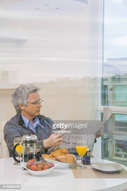 Man reading newspaper over breakfast