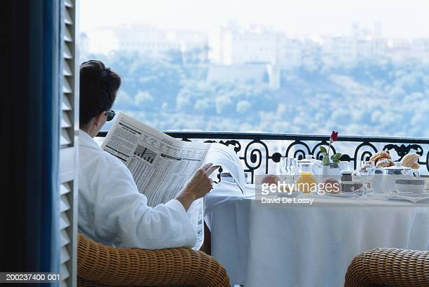 Man reading newspaper, sitting in front of breakfast table