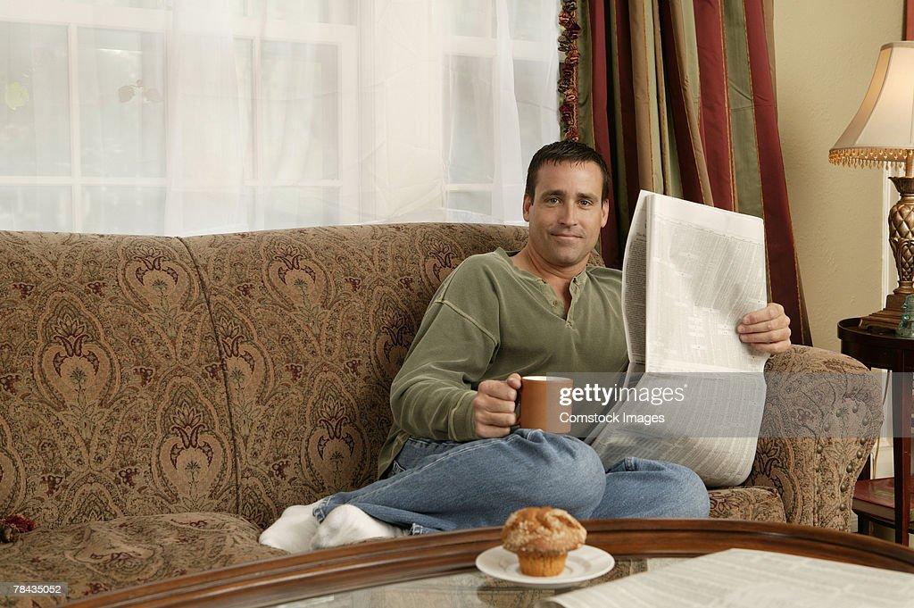Man reading newspaper while drinking coffee : Stockfoto