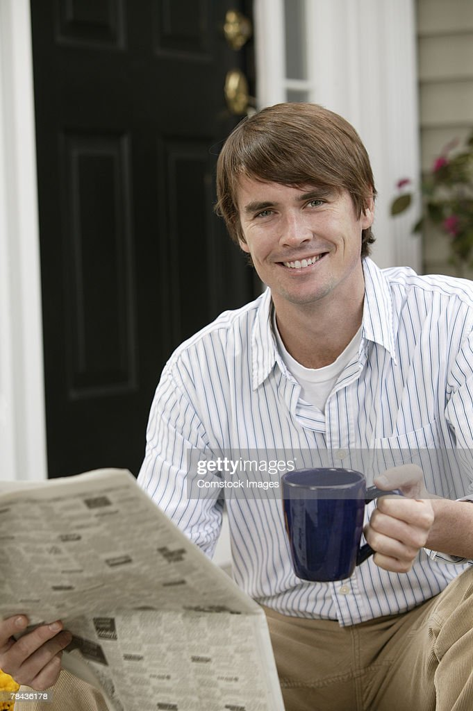 Man reading newspaper while drinking coffee : Stockfoto