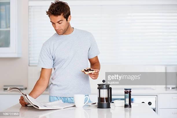 Mann liest Zeitung und Essen Frühstück