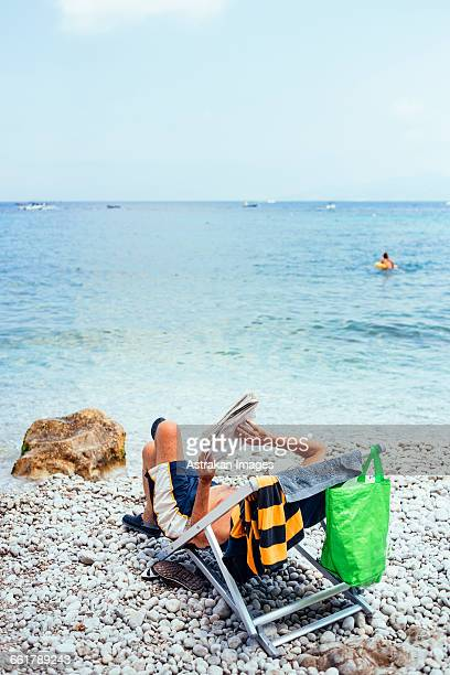 Man reading newspaper while relaxing on folding chair at sea shore