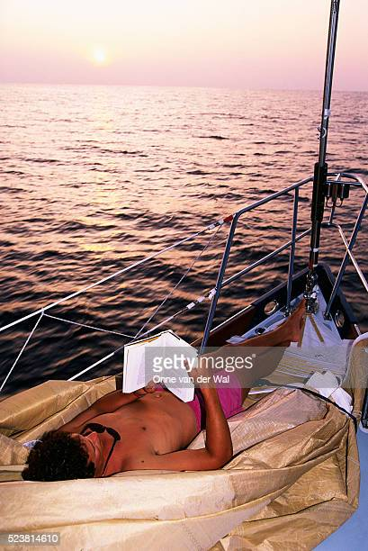 Man Reading on a Sailboat's Prow