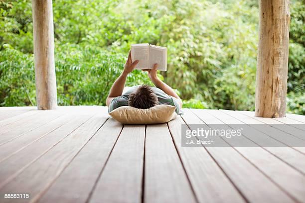 man reading on porch in remote area - lesen stock-fotos und bilder