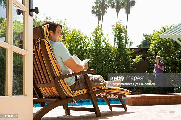 Man reading on striped deck chair