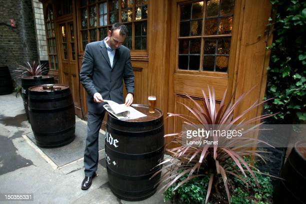man reading outside ye olde mitre pub. - mitre stock photos and pictures