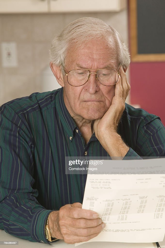 Man reading paperwork : Photo