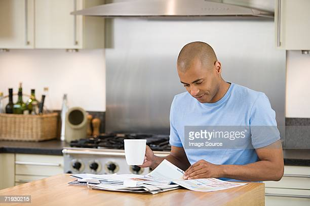 Man reading post in kitchen
