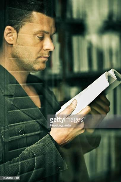 Homme lecture, vu à travers une fenêtre