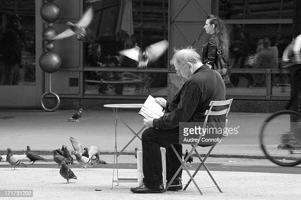 CONTENT] Man reading sitting at table in the Broadway Pedestrian Mall will pigeons flutter around him Midtown Manhattan New York City