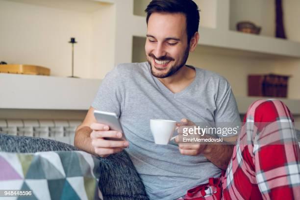 Man leest sms-berichten terwijl u geniet van koffie thuis