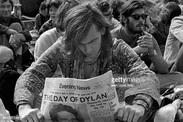 Man reading the evening newspaper featuring cover photographs of Bob Dylan during a concert at the International Pop and Rock Festival of the Isle of...