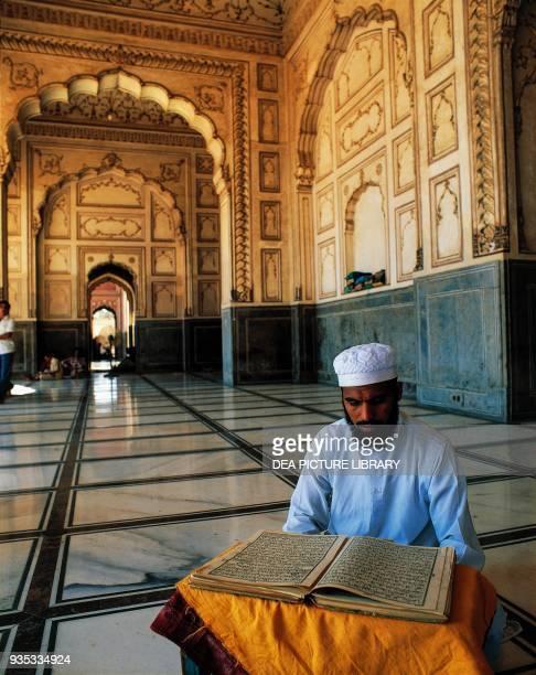 Man reading the Koran in the Badshahi mosque Lahore Punjab Pakistan