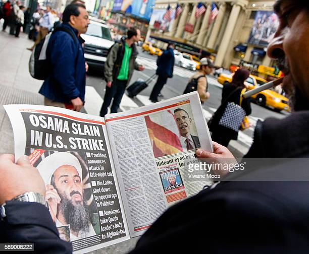 A man reading the newspaper about Osama bin Laden's capture and death Got Him and Rot in Hell are some of the headlines