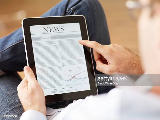 Man reading the newspaper on digital tablet