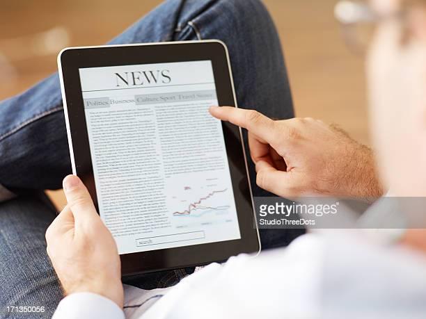 Homme lisant le journal sur Tablette numérique