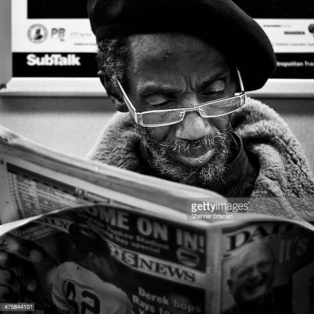 Man reading the newspaper on the subway in New York City