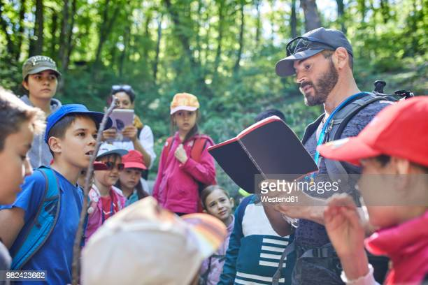 man reading to kids on a field trip in forest - field trip stock pictures, royalty-free photos & images