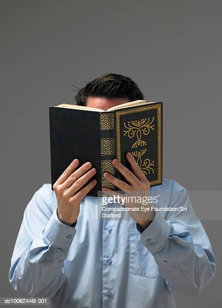 Man reading torah, holding book over face