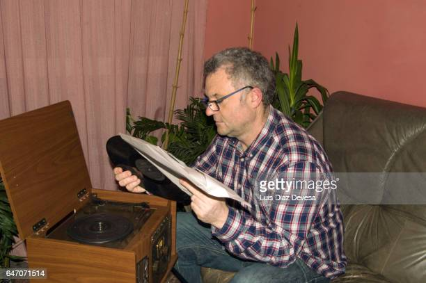 man reading vinyl record cover - un solo hombre stock photos and pictures