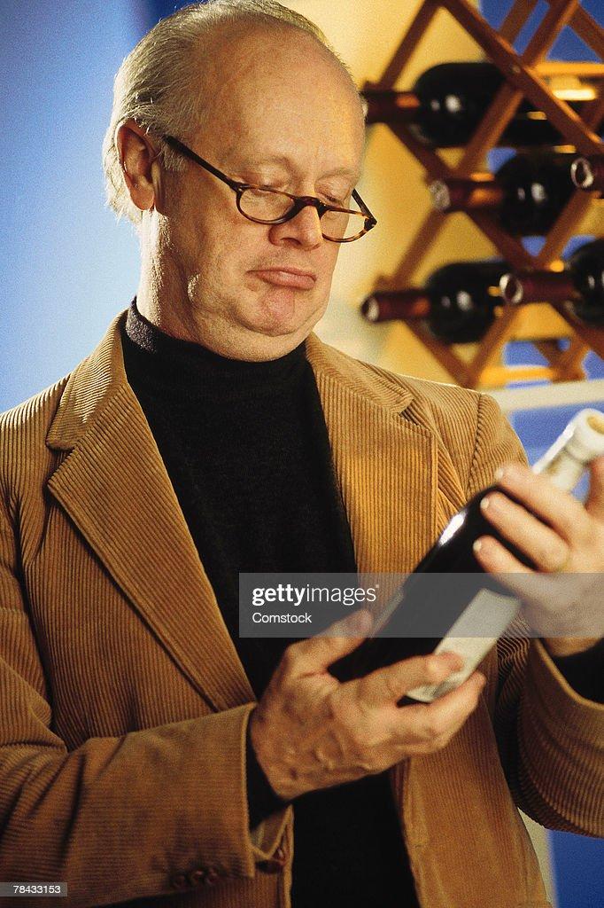 Man reading wine bottle label : Stockfoto