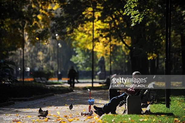A man reads a book as he plays with a kid at the boulevard in Moscow on October 5 2010 AFP PHOTO / DMITRY KOSTYUKOV