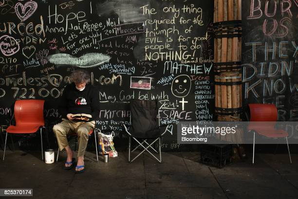A man reads a book in front of a chalkboard wall at a camp for the homeless at Martin Place in Sydney Australia on Thursday Aug 1 2017 On the...