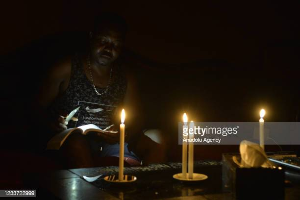 Man reads a book in the dark during power cuts due to the fuel shortage and problems in the supply of fuel, which is traded in dollars, in Beirut,...