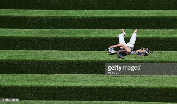 A man reads a book in the sunshine on steps covered in artificial grass on July 10 2013 in London England