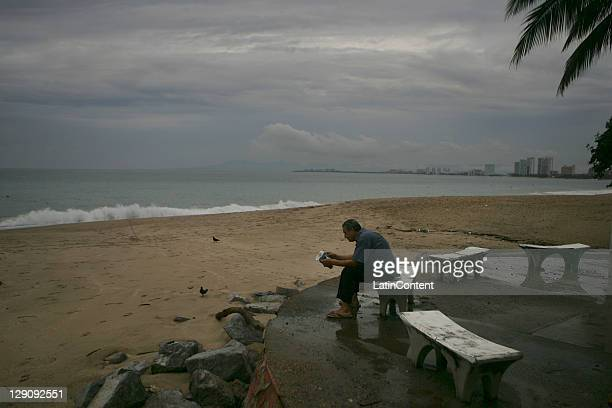 Man reads a book next to the beach before the arrival of the Hurricane Jova October 11, 2011 in Puerto Vallarta, Mexico.