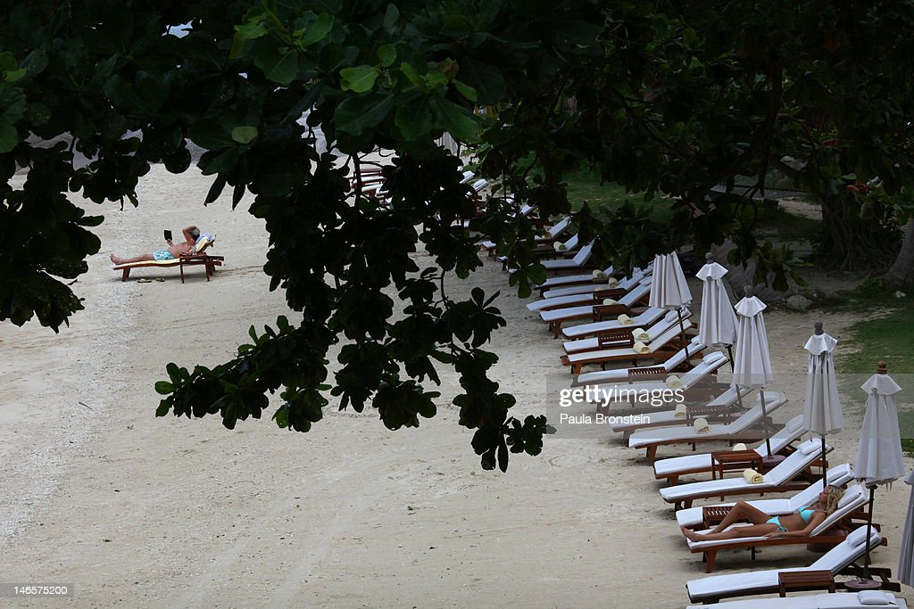 A man reads a book on the beach at the Kamalaya Wellness Sanctuary June 18, 2012 . Thailand's official tourism body, the Tourism Authority of Thailand (TAT) has set itself the ambitious target of attracting more than 20 million tourists in 2012. According to TAT, In April, Thailand welcomed 1,659,021 international tourists which is a slight increase of 6.87% over the same in 2011.