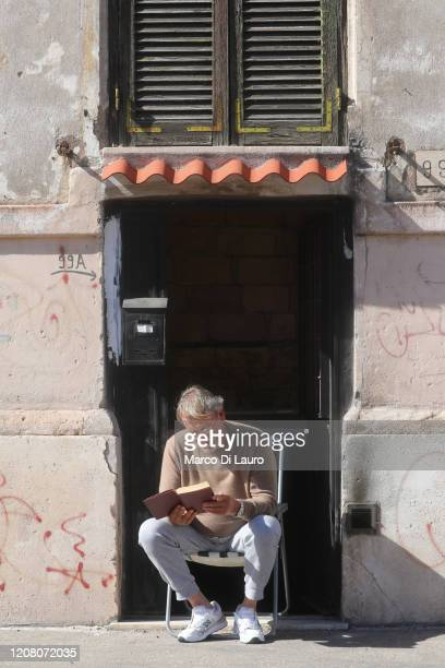 A man reads a book on the front door in the middle of the street during lockdown on March 23 2020 in Rome Italy As Italy extends its nationwide...
